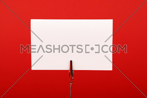 Blank white cardboard sign with copy space on metal note holder over red paper background, front side view