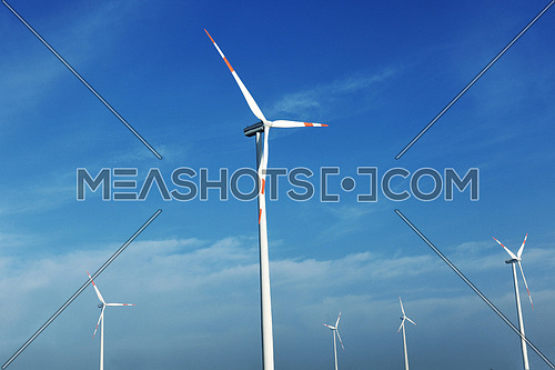 wind turbine  generating eco friendly renewable  electricity energy on blue sky