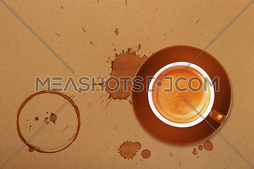 Brown cup full of espresso coffee on saucer, with ring coffee stains and drops on brown paper parchment background, elevated top view, directly above
