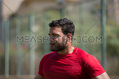 young middle eastern man is refreshed after a hard workout pouring water over themselves to summer heat