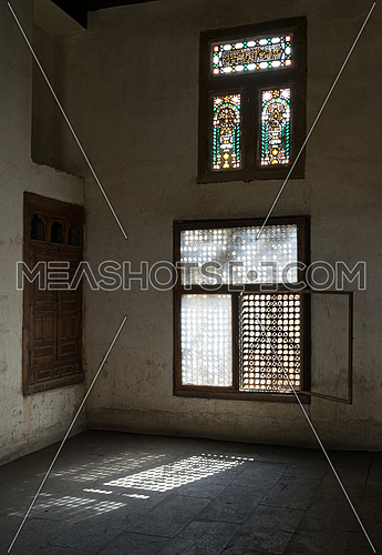 Old abandoned dark damaged dirty room with two wooden broken ornate windows covered by interleaved wooden grid (mashrabiya)