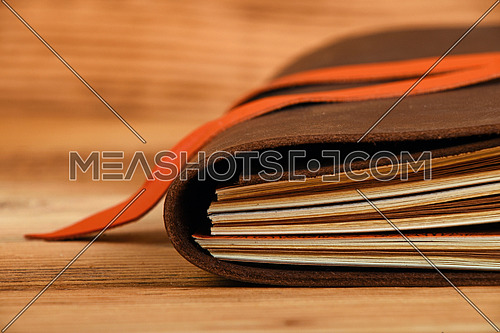 Handmade paper diary notebook in brown leather cover with orange bookmark over old vintage wooden table surface background