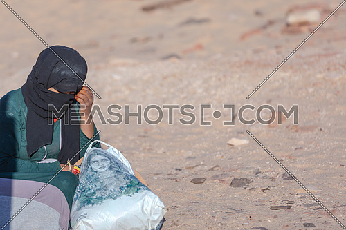 mid Shot for a bedouin woman sits on sands from Sinai Trail at day.