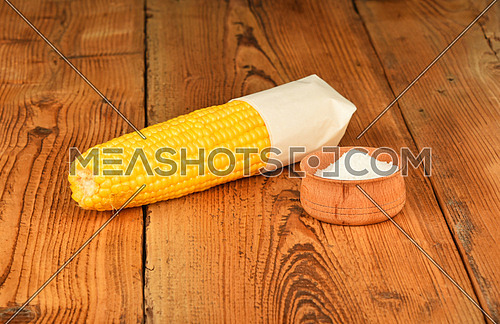 One open fresh yellow corn cob and salt in cup on brown vintage wooden surface