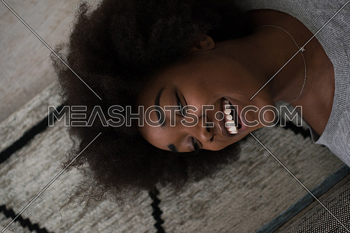 Close up face of a beautiful african american woman  lying on carpet