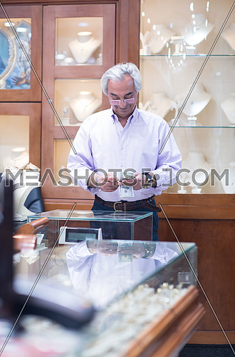 Senior middle eastern successful owner works in his luxury jewelry store