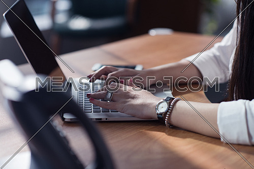 Close up of a young female executive hands typing on a computer in a modern office