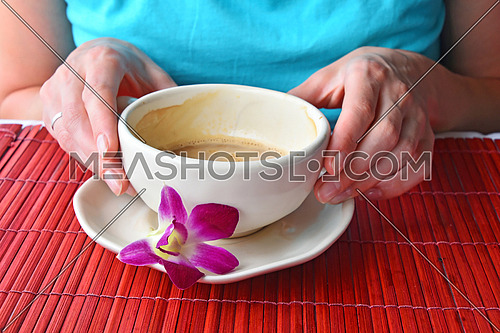 Woman two hands holding half empty latte coffee cup with orchid flower at porcelain saucer