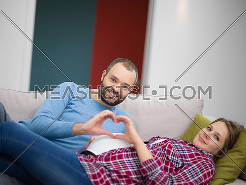 Happy man and pregnant woman showing heart sign with fingers while relaxing on the sofa at home