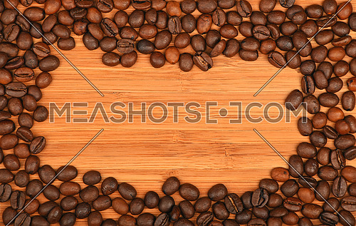 Roasted Arabica coffee espresso beans shape solid border frame over wooden bamboo board background
