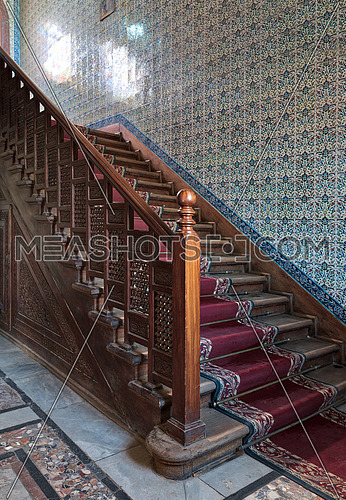 Wooden staircase with ornate red carpet, decorated wooden balustrade and Turkish ceramic tiles wall at the Residence hall, Manial Palace of Prince Mohammed Ali