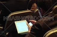 Medium shot from behind for a male business man Using a mobile device at a meeting