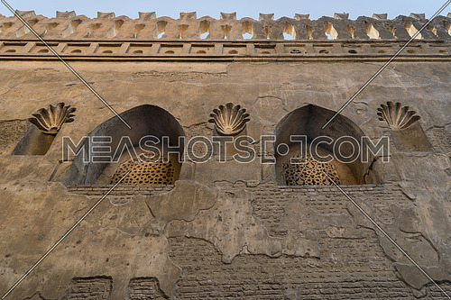 Two perforated arched stucco window decorated with floral patterns, one of the traditions of the Mamluk era, Outer wall of Mosque of Ibn Tulun, Sayyida Zaynab district, Medieval Cairo, Egypt