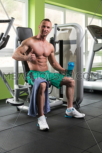 Muscular Man Resting After Exercise And Drinking From Shaker While Showing Thumbs Up
