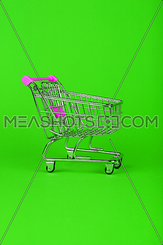 Close up empty toy metal supermarket shopping cart over vivid green background with copy space, low angle side view