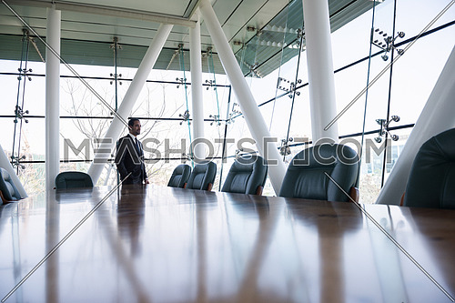 young businessman standing alone in modern conference room office