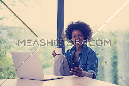Young african american woman smiling sitting near bright window while looking at open laptop computer on table and holding white mug in her luxury home