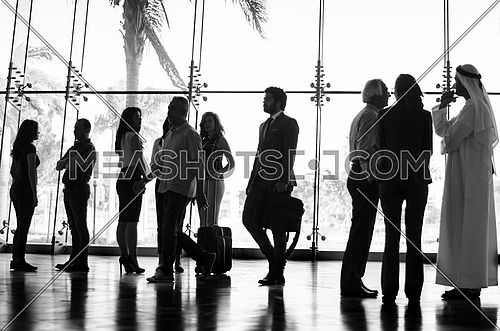 groups of people in meetings while two guys cross the hall way