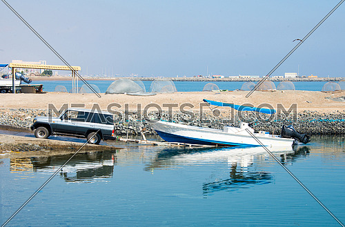 An SUV  launching a fishing boat in the water