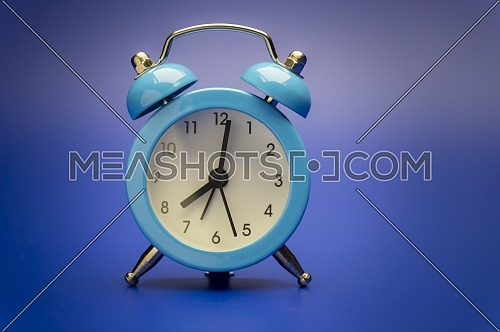 Blue twin bell analog alarm clock over a colorful blue background with copy space