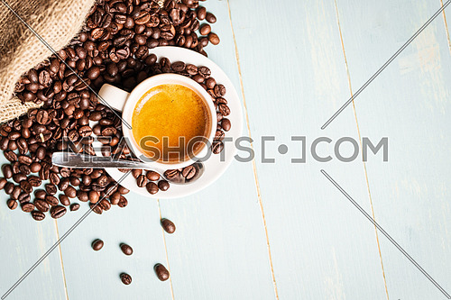 White cup of coffee,teaspoon and coffee bean on green background. Copy space. Top view.