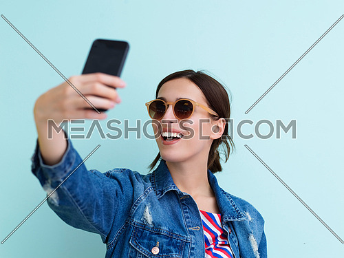 Portrait of young girl taking selfie on blue background. Female model wearing sunglasses and holding phone representing modern fashion and technology