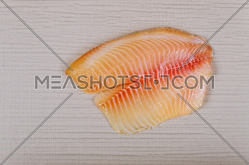 Raw tilapia fish fillet with ready for cooking on cutting board