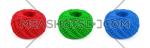 Three colorful multicolor small round coil bobbins of natural red, green and blue twine hessian burlap jute rope isolated on white background, close up, high angle view