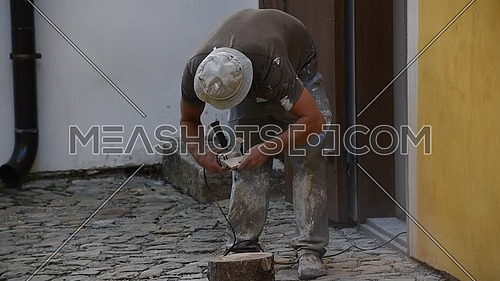 Close up of working man cutting and shaping ceramic tile with angle grinder, low angle view