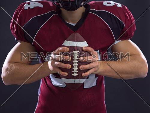 Closeup Portrait of a strong muscular American Football Player isolated on gray