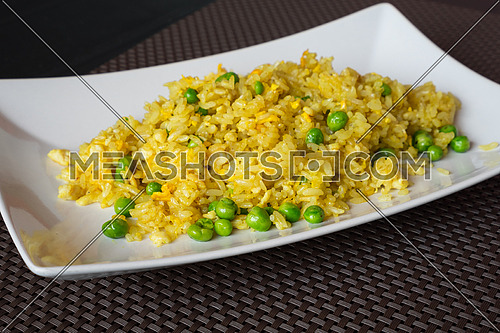 Fried curry rice with peas served on white plate at restaurant, brown background.