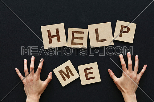 Close up HELP ME wooden letters sign with woman hands raised up over black chalkboard background