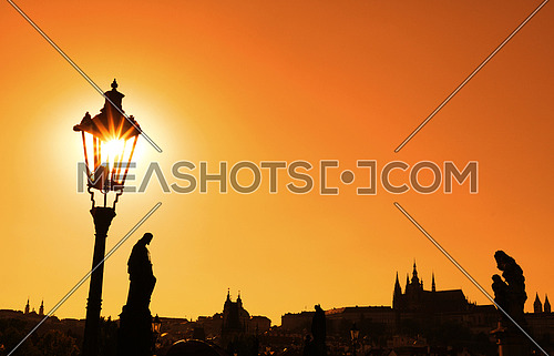 Sunset backlit silhouettes of street lamp post, statues and roofs of cityscape skyline at Charles Bridge in Prague, Czech Republic