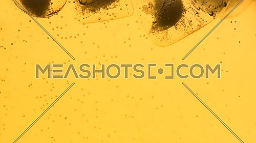Extreme close up sparkling wine, soda water or lemonade with ice cubes in glass, low angle side view, slow motion