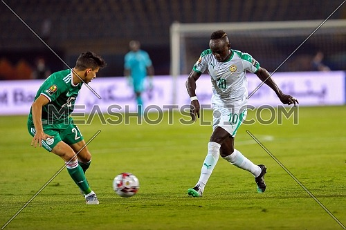 27 June 2019, Egypt, Cairo: Senegal's Sadio Mane (R) and Algeria's Mandi Belaili battle for the ball during the 2019 Africa Cup of Nations Group C soccer match between Senegal and Algeria at the 30 June Stadium.