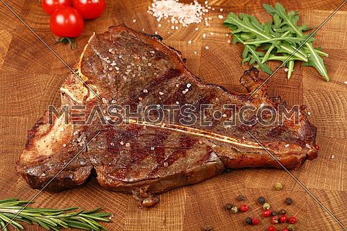 Close up one big grill roasted T-bone porterhouse beef steak with rib bone served on wooden cutting board, elevated high angle view