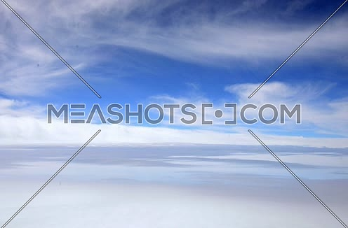 arial view from airplane window showing blue sky and clouds