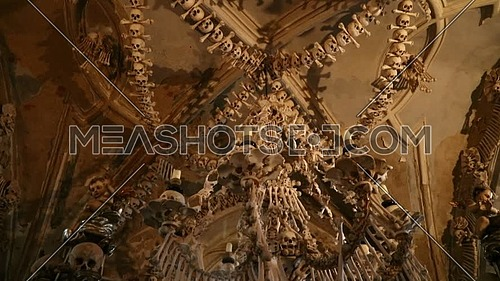 Low angle view tilt of human skulls and bones decoration of Kostnice, The Sedlec Ossuary near Kutna Hora in Czech Republic