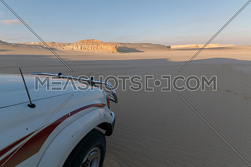 Desert Safari 4*4 white car in Nature Reserve Desert Dunes landscape with blue sky , Fayoum , Egypt