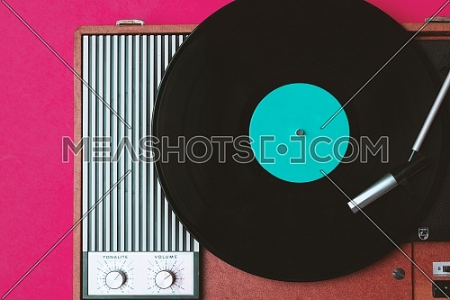 Vintage vinyl player and turnable on a fuchsia background. Entertainment 70s. Listen to music. Top view.