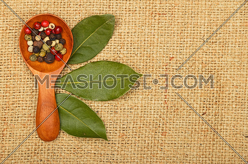 Three green bay laurel leaves and mix of peppercorn in wooden scoop on brown burlap jute canvas background