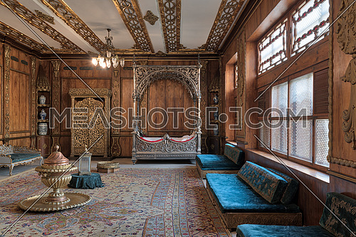 Cairo, Egypt - December 2, 2017: Manial Palace of Prince Mohammed Ali Tawfik. Residence of prince's mother with golden ornate niche, silver bed, golden wardrobe, blue couches, ornate wooden wall and ceiling