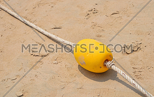 Yellow polystyrene sea marker buoy with cable tow on wet sand sea beach