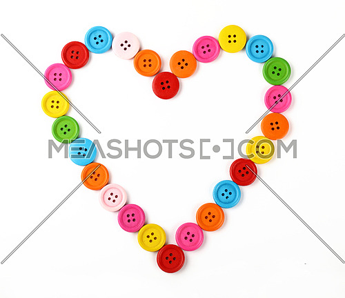 Heart shaped frame of colorful multicolor round painted wooden handmade sewing buttons isolated on white, close up, elevated top view