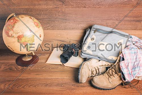 Front view of globe,camera,book,bag,boots and shirt, wooden background,vintage look for travel concept.