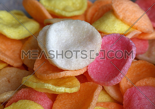 Heap of multicolor Asian traditional shrimp cracker chips close up, high angle view