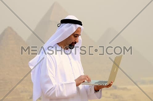 Emiratie man at the pyramids using laptop
