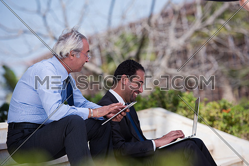 Business executives sitting on stairs of a corporate building discussing business and working online with tablet