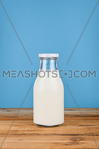 Close up one glass bottle full of fresh milk on wooden table over blue background, low angle, side view