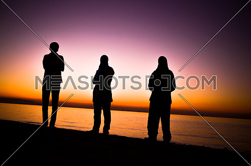 3 friends standing at the beach enjoying the sunset